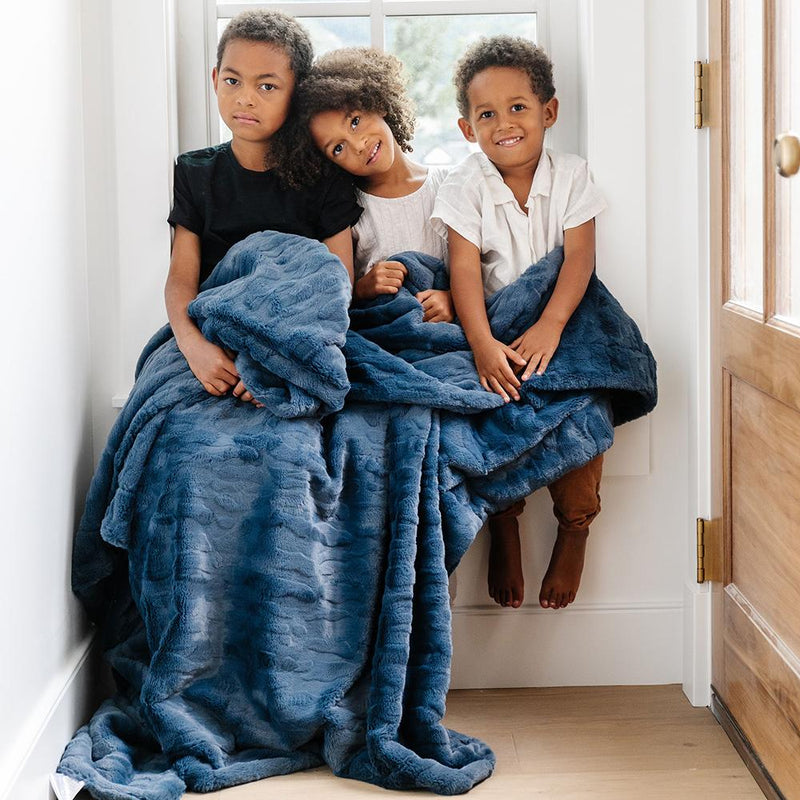 Family gathers in kitchen with young boy sitting on the counter wrapped in fuzzy blue blanket