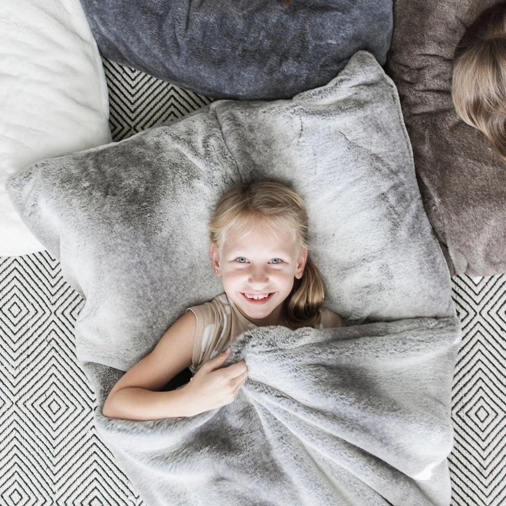 Little girl cuddles in her gray and white faux fur sleeping bag.