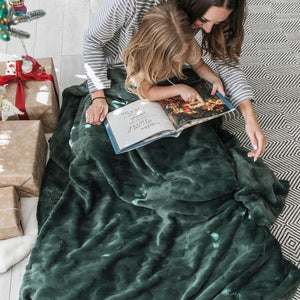 Mom reads story book to her daughter while snuggled under a deep green soft throw blanket.