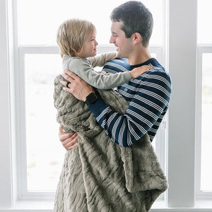 Dad holds his son that is wrapped in warm brown throw blanket.