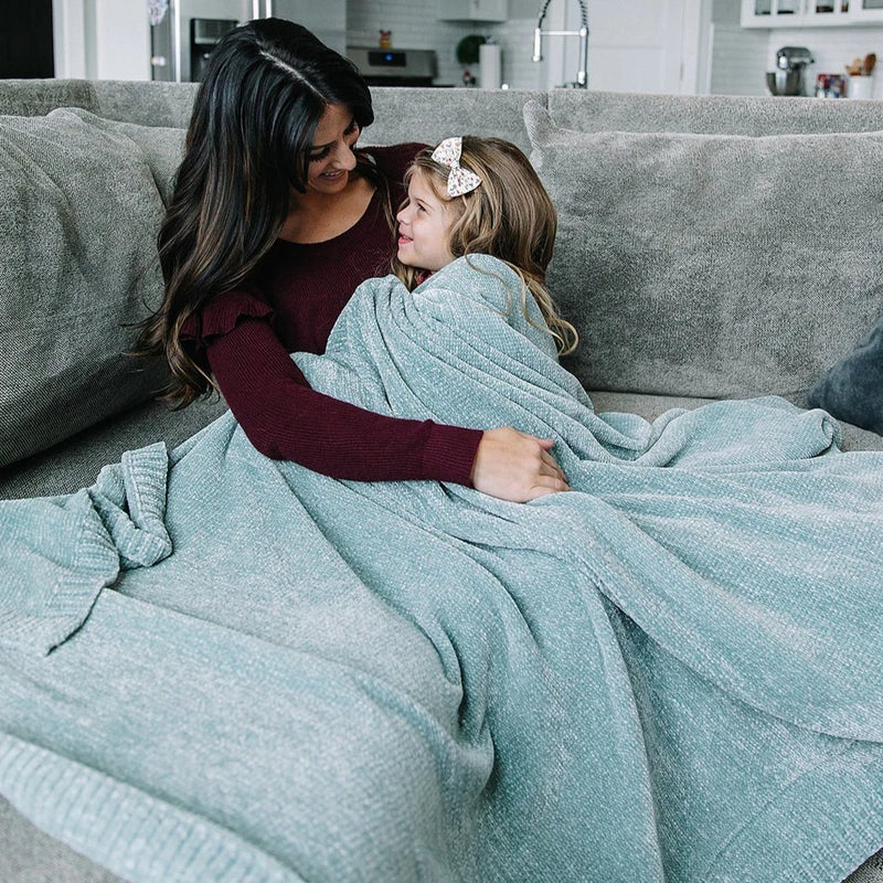 Mom cuddles her daughter while sitting on the couch wrapped in stretchy light blue blanket.