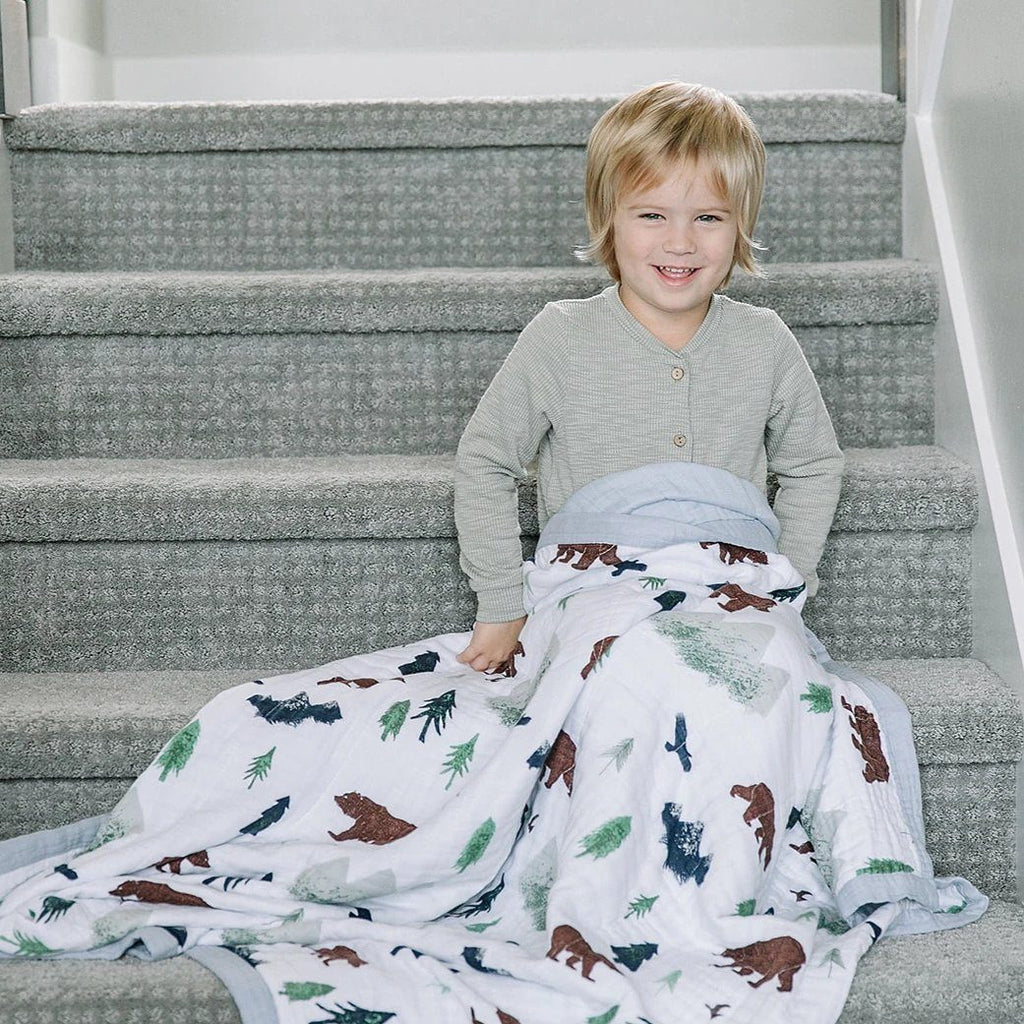 Little boy sits on the stairs with his four layer muslin blanket with birds, bears, mountains, trees, and birds.