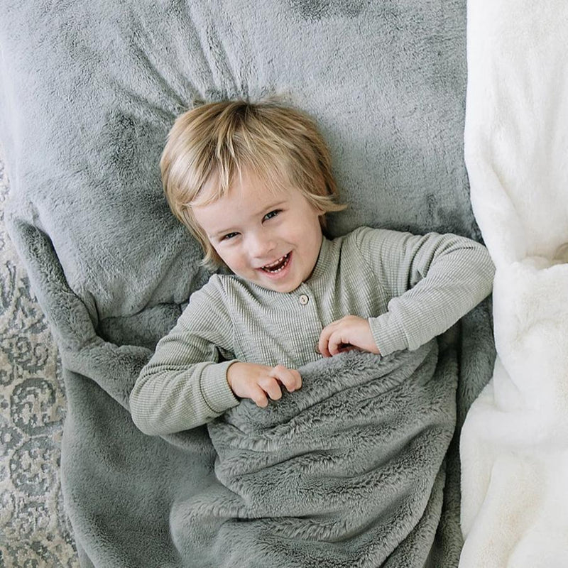 Little boy snuggles in his light gray faux fur sleeping bag.