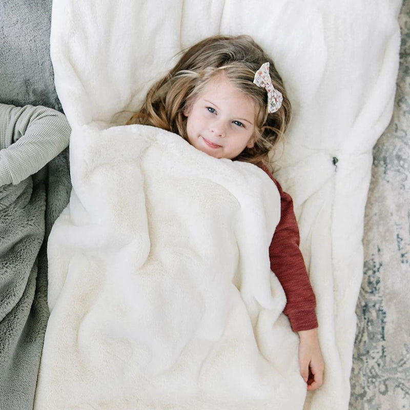 Little girl cuddles in her ivory faux fur sleeping bag.