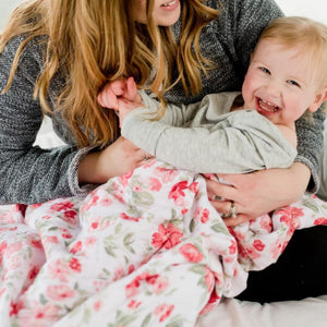 Mother playing with child wrapped in a beautiful pink baby quilt. Muslin fabric, floral print.