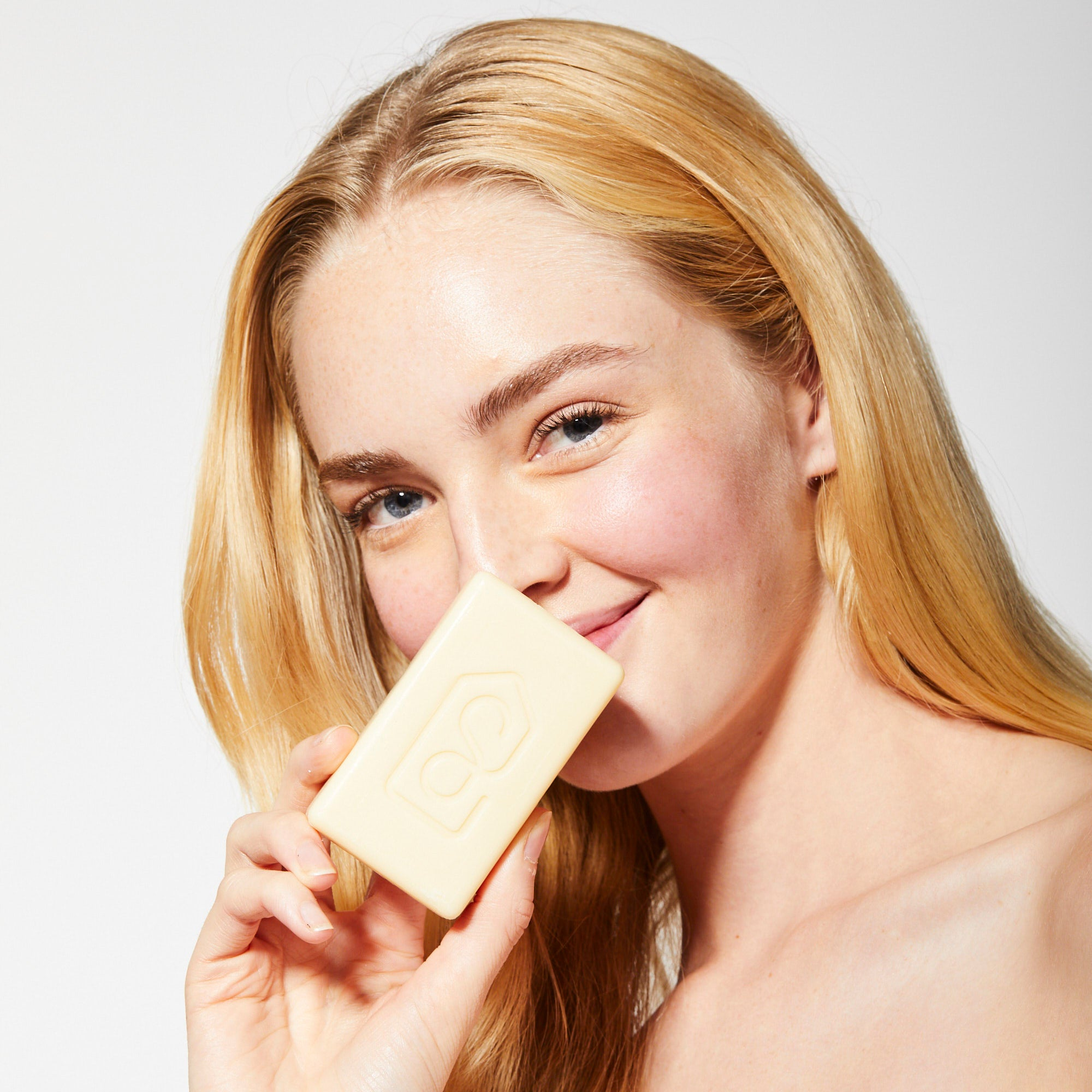 Bamboo Hydrate Bar Soap, woman holding bar up to nose to delight in fragrance