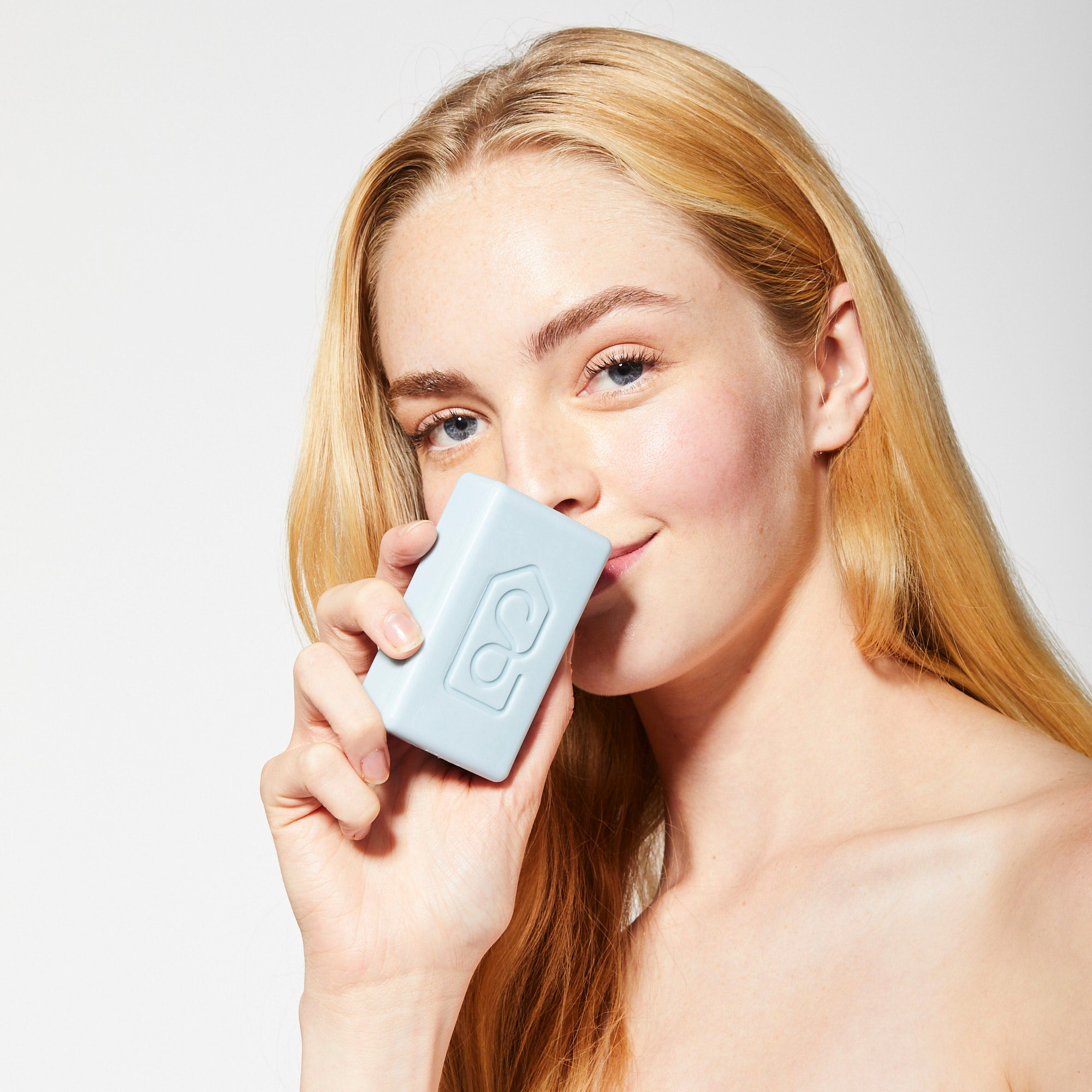 Herbal Blend Bar Soap: woman holding the bar to her nose to smell the fragrance