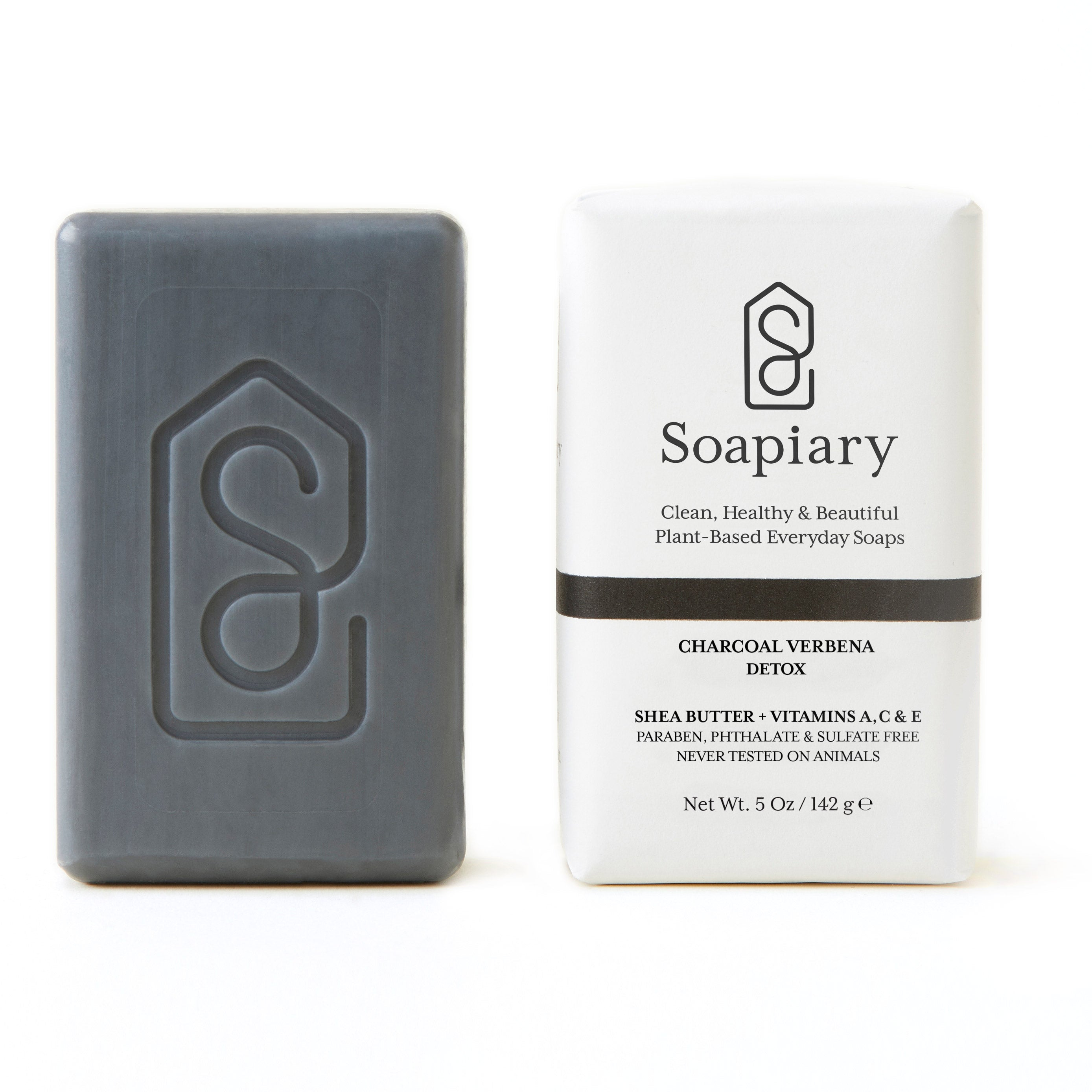 Soapiary Charcoal Verbena Detox Bar Soap, 5oz: Grey-colored, unwrapped soap bar standing next to wrapped soap bar to show how it looks packaged. Rectangular soap is wrapped in white paper packaging with black lettering and black stripe.