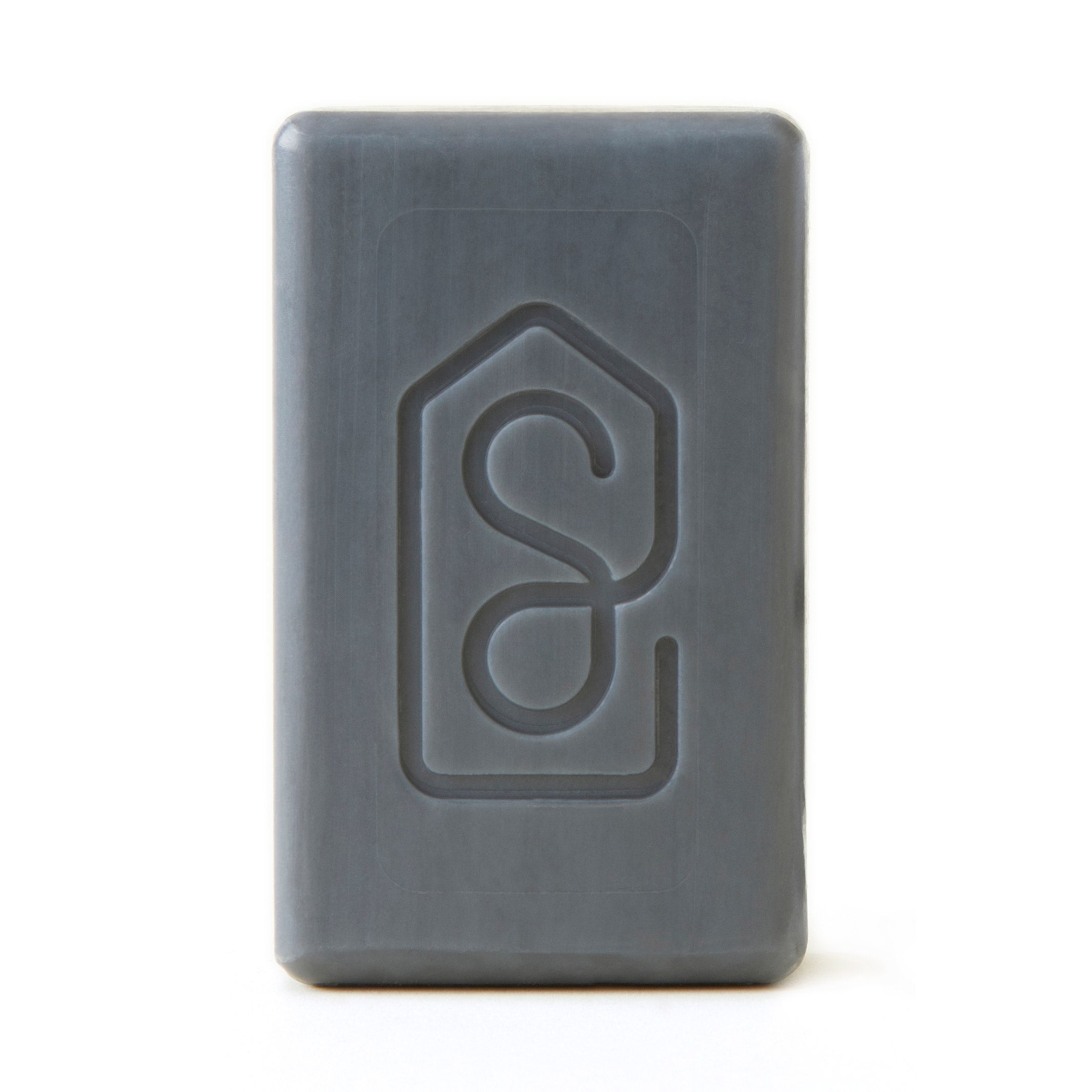 Soapiary Charcoal and Verbena Bar Soap: Rectangular bar soap shown unwrapped to show grey coloring with stamped logo on bar.