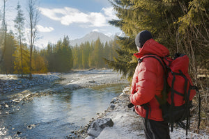 man in red down jacket by river and mountains