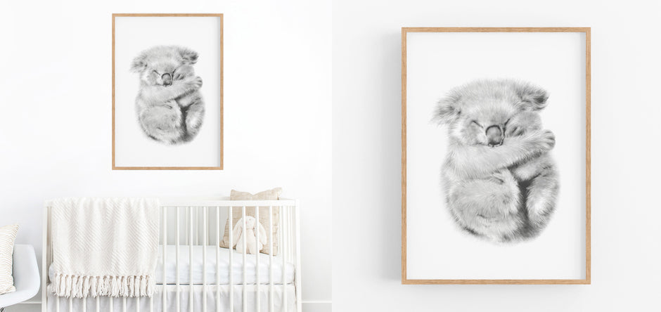 black and white koala art print hanging in a nursery above a white cot