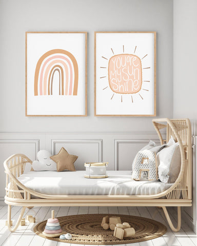 gender neutral rainbow and sunshine art print hanging in a kids room above a cane bed