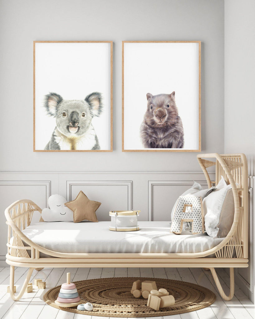 koala and wombat prints hanging in a kids room above a cane bed