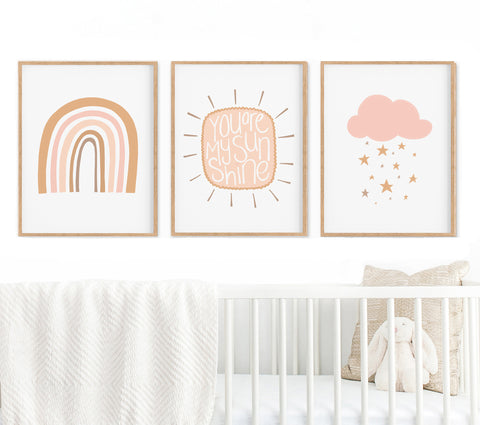 Set of 3 Rainbow Sunshine and Cloud Prints in timber frames hanging above a cot in a nursery