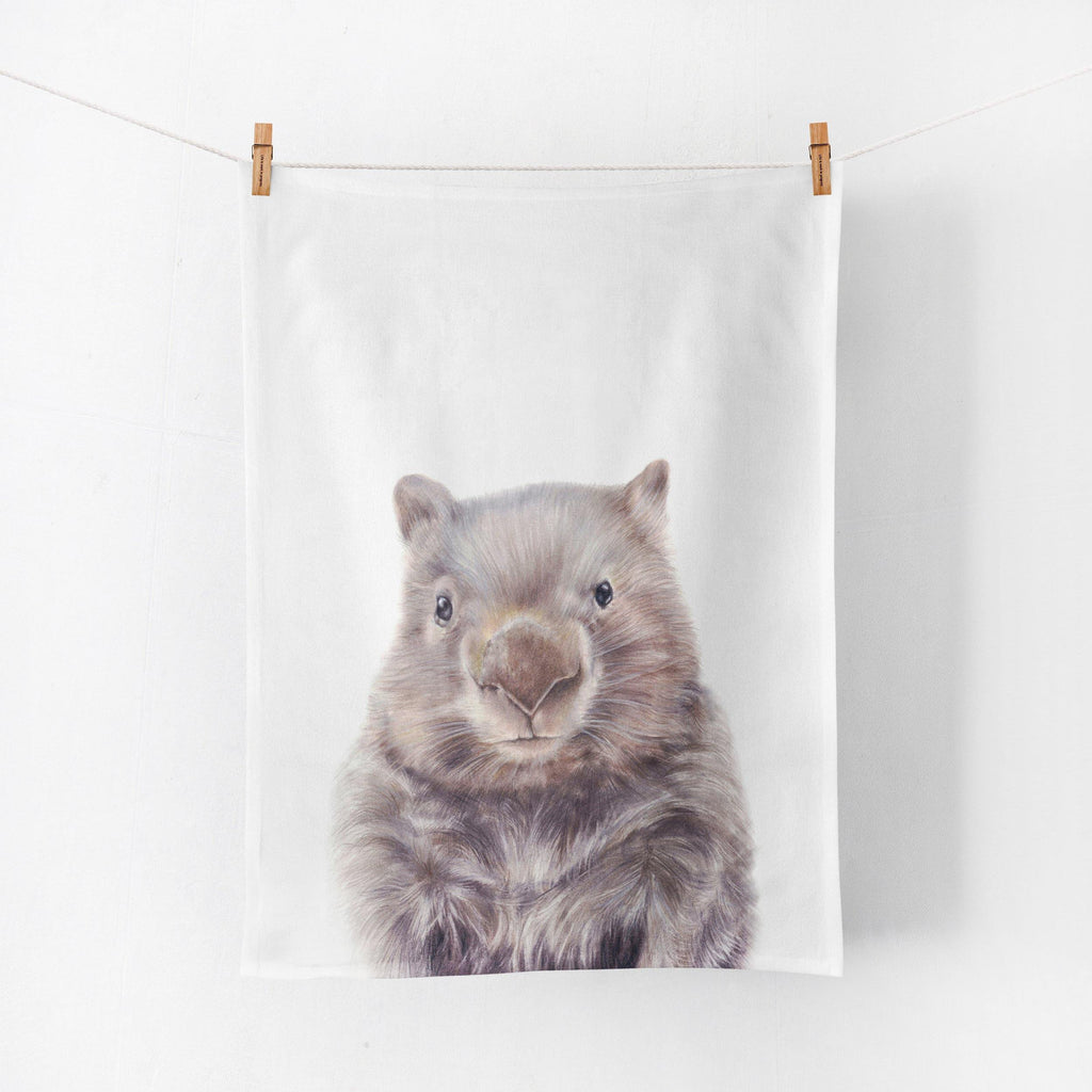 cotton tea towel printed with a wombat illustration, hanging on a line by pegs