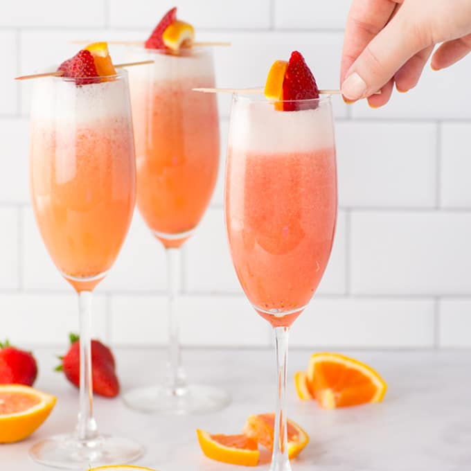 strawberry orange mimosas in champagne flutes