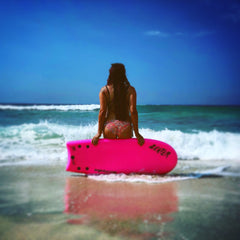 Woman sitting in pink body board