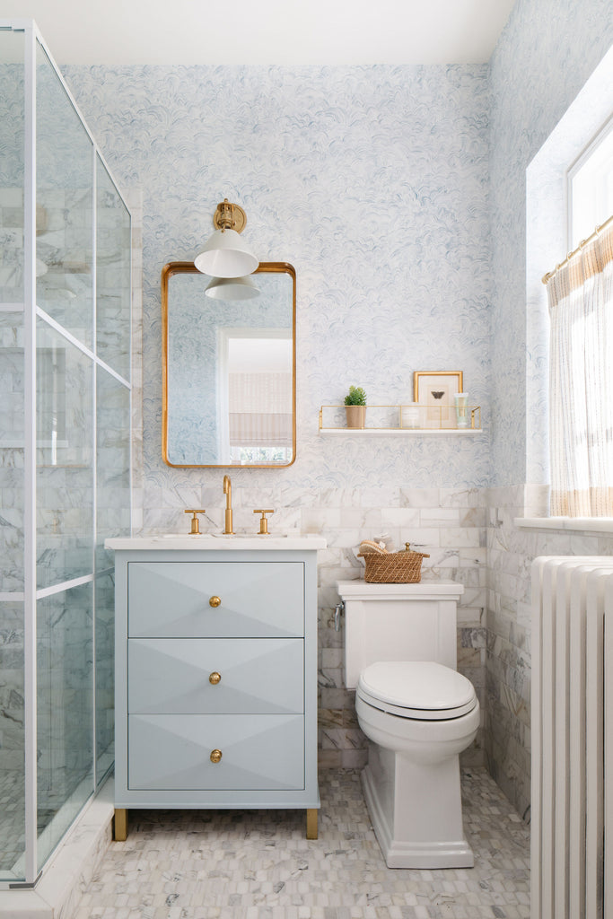 pale blue luxury bathroom with brass accents