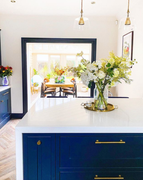 bright sunny kitchen with blue cabinets and solid brass cabinet handles, flowers on island, view to orangery
