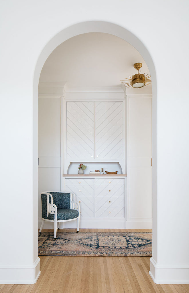 white curved archway leading to white closet cabinets with chair and rug