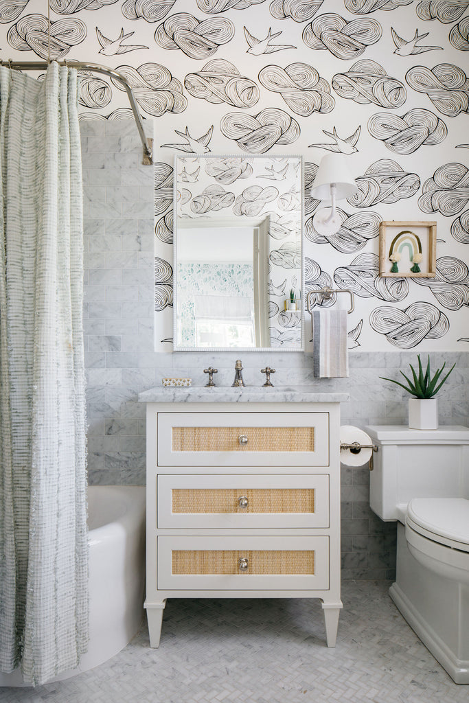 grey and white en-suite bathroom with cloud and dove wallpaper, mirror, marble and rattan vanity unit