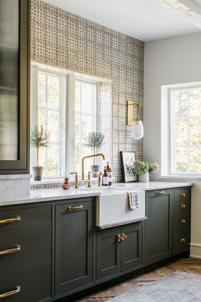 window and kitchen sink, green painted cabinets, brass hardware and tap