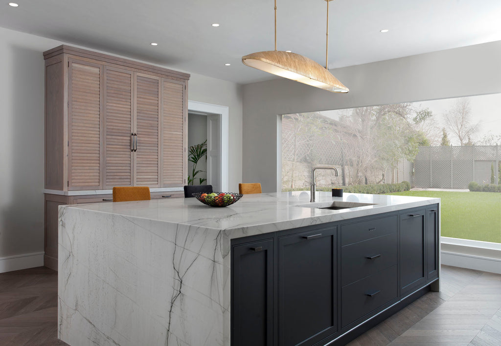 minimal kitchen island with marble surface and dark painted cabinetry
