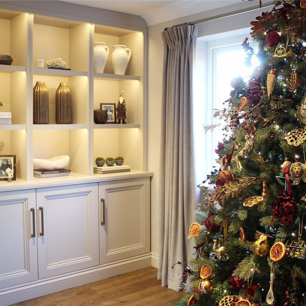 styled built in shelves with warm lighting and traditional christmas tree