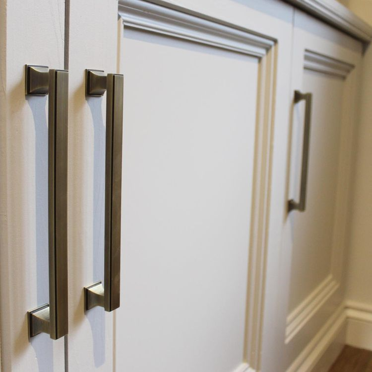 close up of antique brass cabinet pull handles on neutral painted cupboards