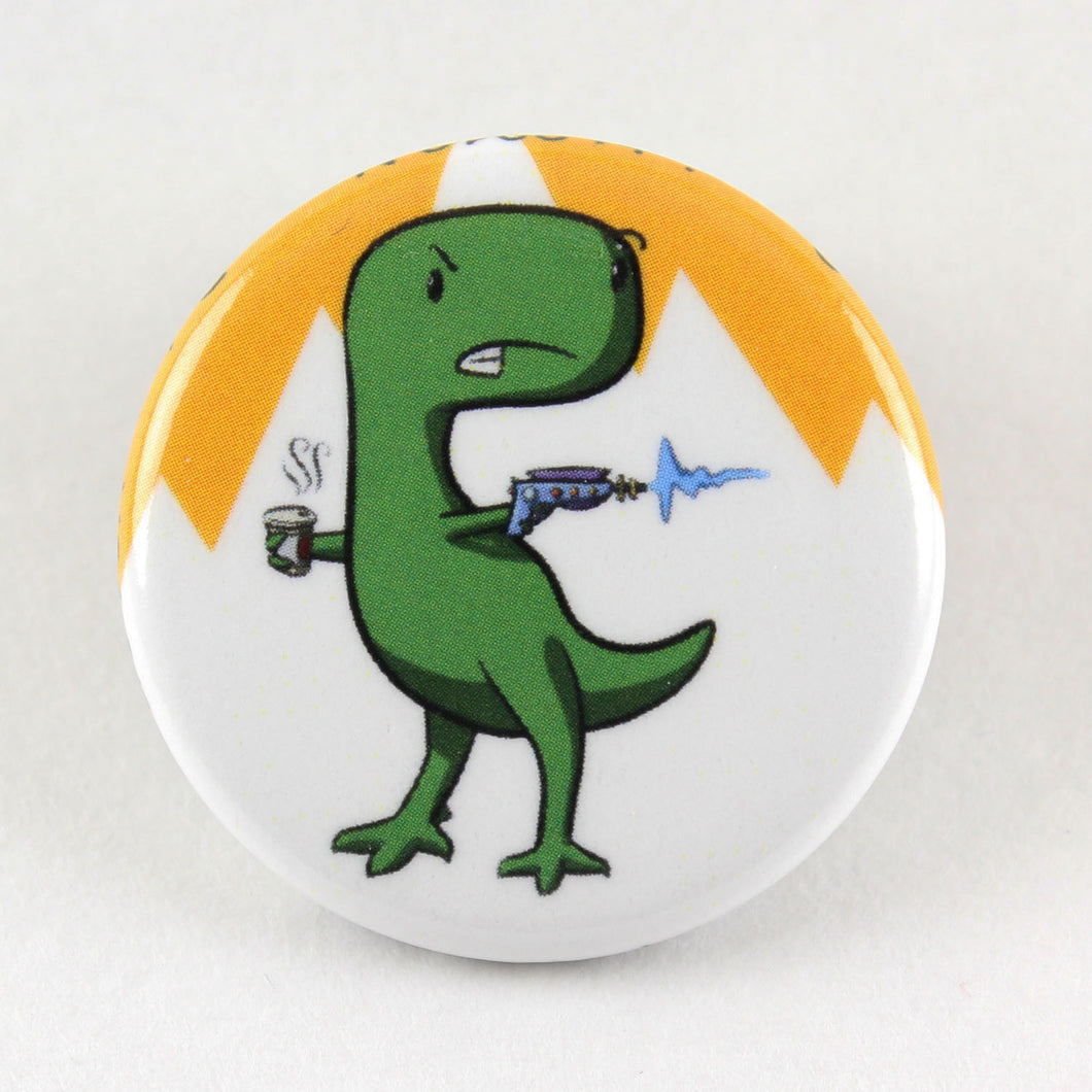 A button pin feature a stern looking T-Rex holding a latté in one hand and a laser gun in the other