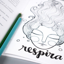 "A page inside of Artisticamente Valiente shows a woman's face with her eyes closed and the word ""respira"" which means ""breathe""."