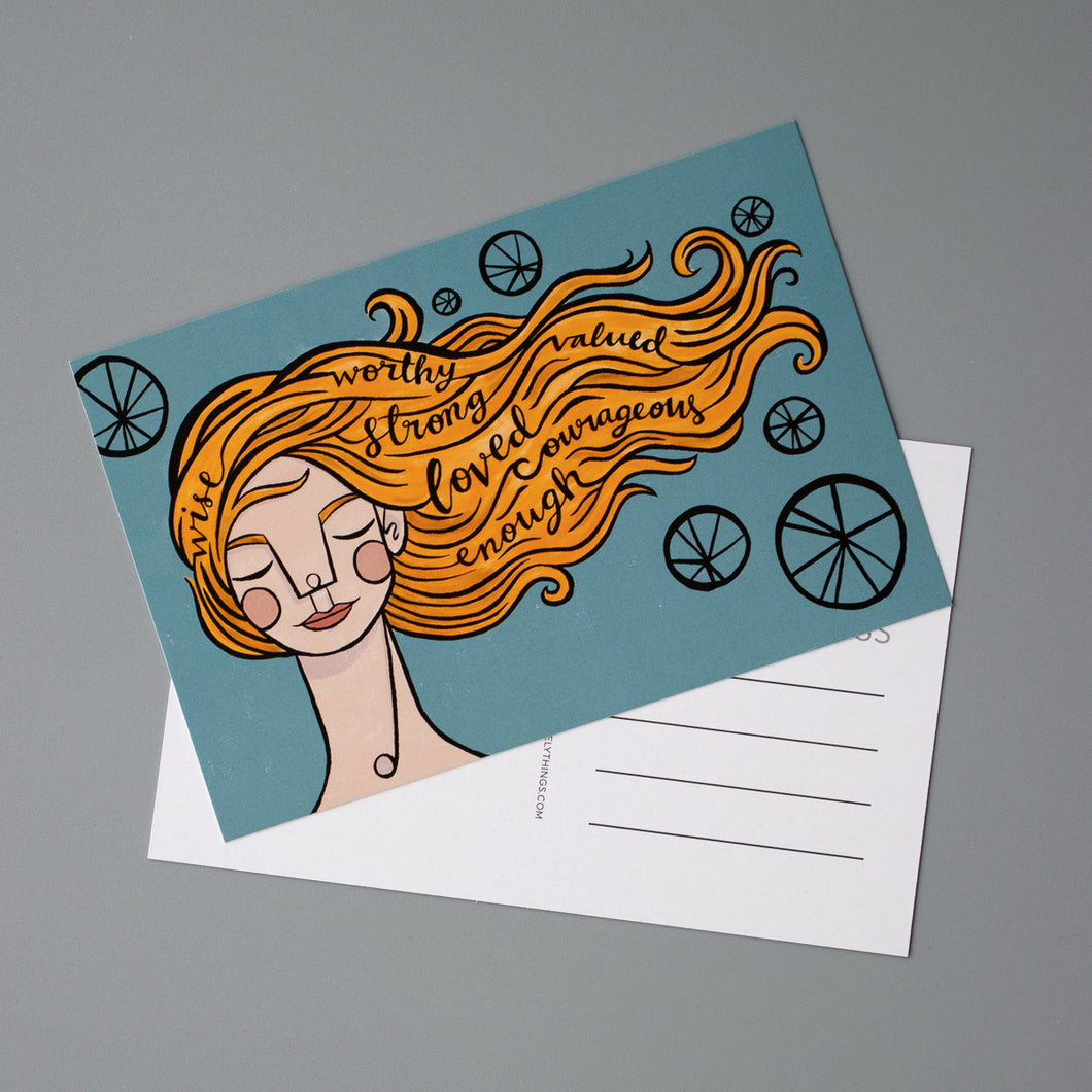 Postcards with the illustration of a woman with orange hair blowing in the wind. In her hair are the words: wise, worthy, strong, valued, loved, courageous, and enough.
