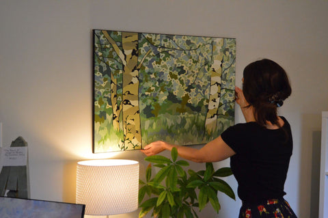 "Paint By Munzy curator Laura Munz hanging ""Laurel Creek Birches"""