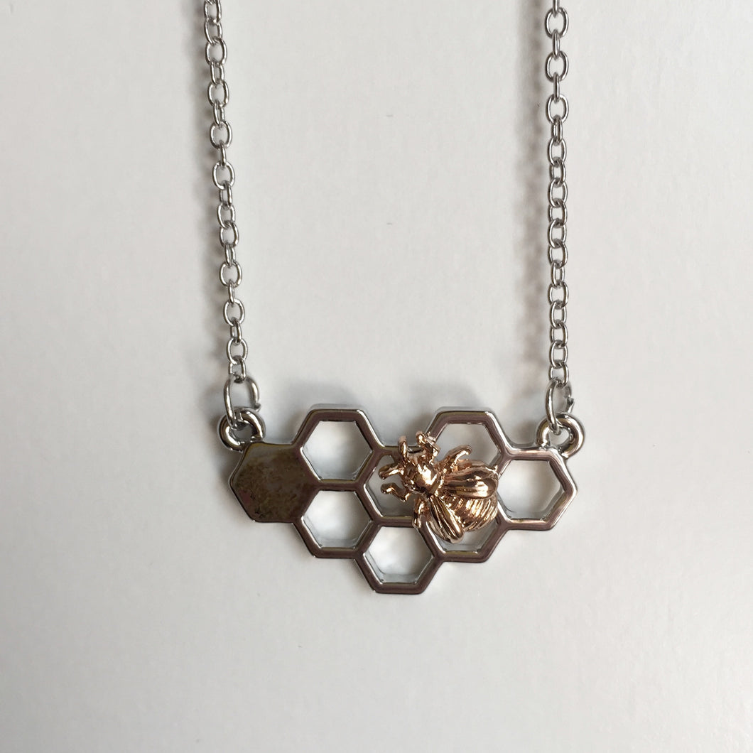 Cute bee and honeycomb pendant necklace in a mixed metal tone, such a fun way to wear this trend. Measures 17