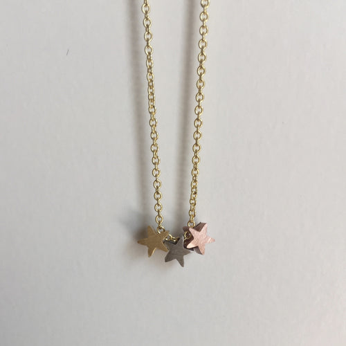 Three dainty stars in gold, silver and rose gold strung on a gold chain. Cute and fun way to rock the mixed metal trend. Measures 16