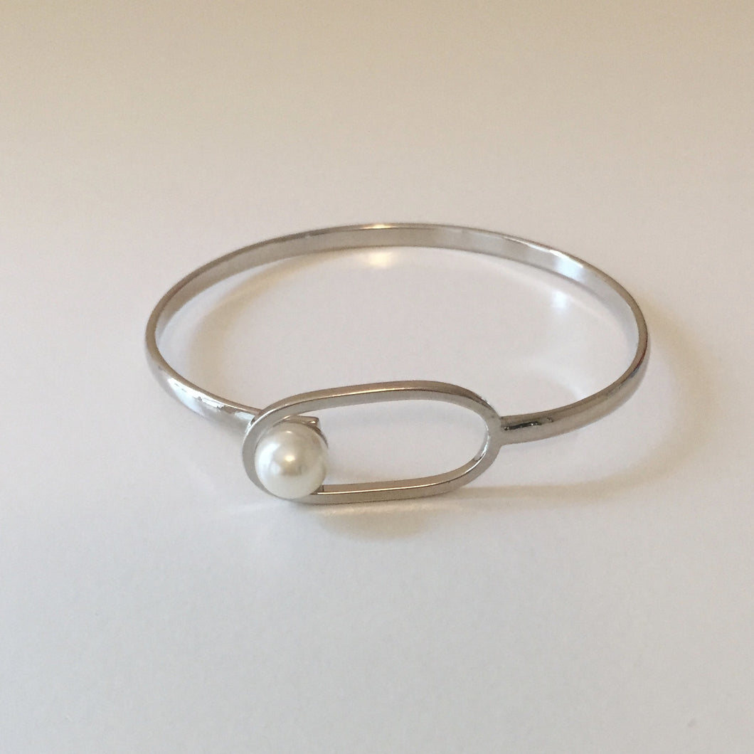 The unique latch is the star of this simple silver bracelet, with a pearlescent stone fastening for closure. Adjustable in size.
