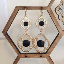 "Tiered gold drop earrings in a chic floral design accented with black stones. Drop measures 2""."
