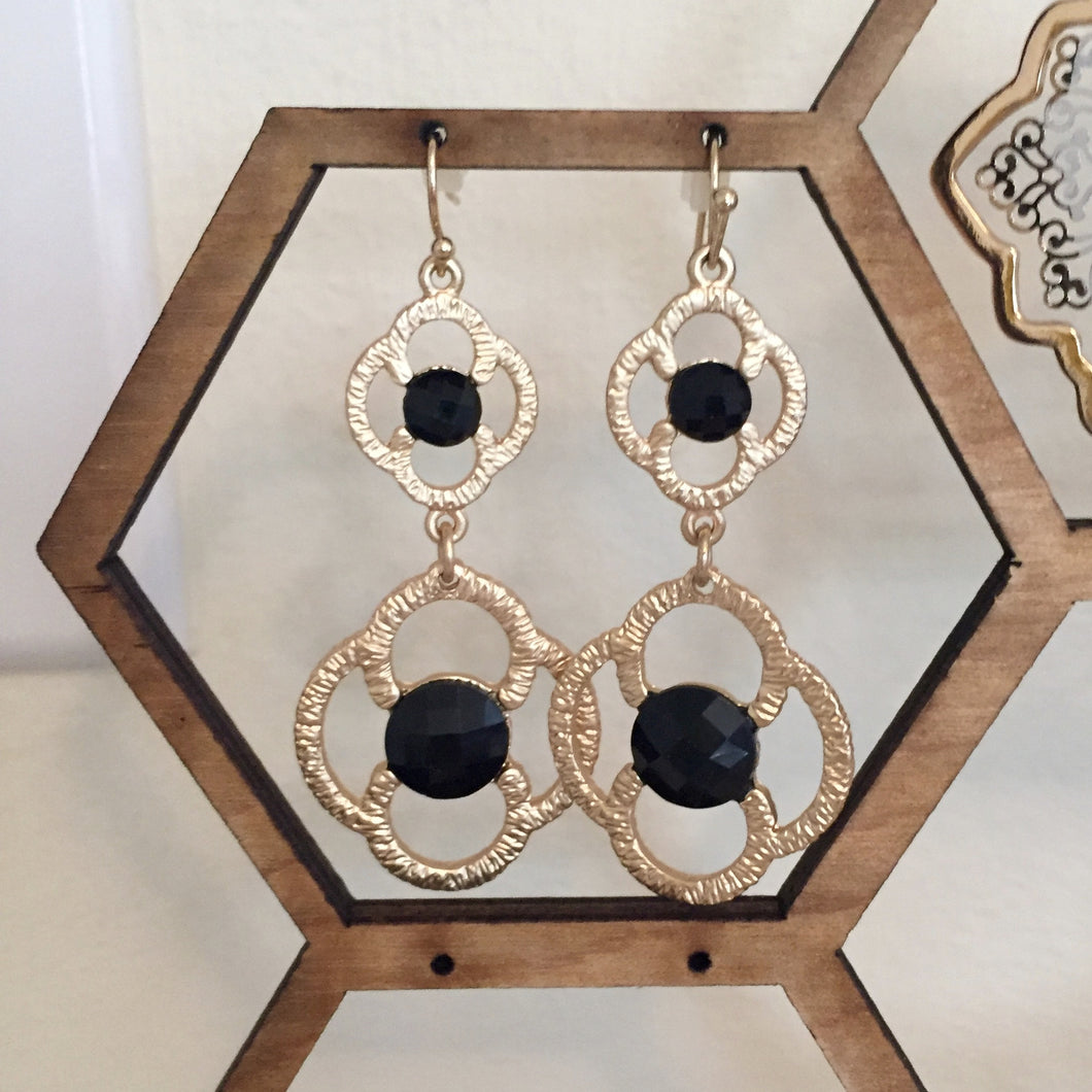 Tiered gold drop earrings in a chic floral design accented with black stones. Drop measures 2