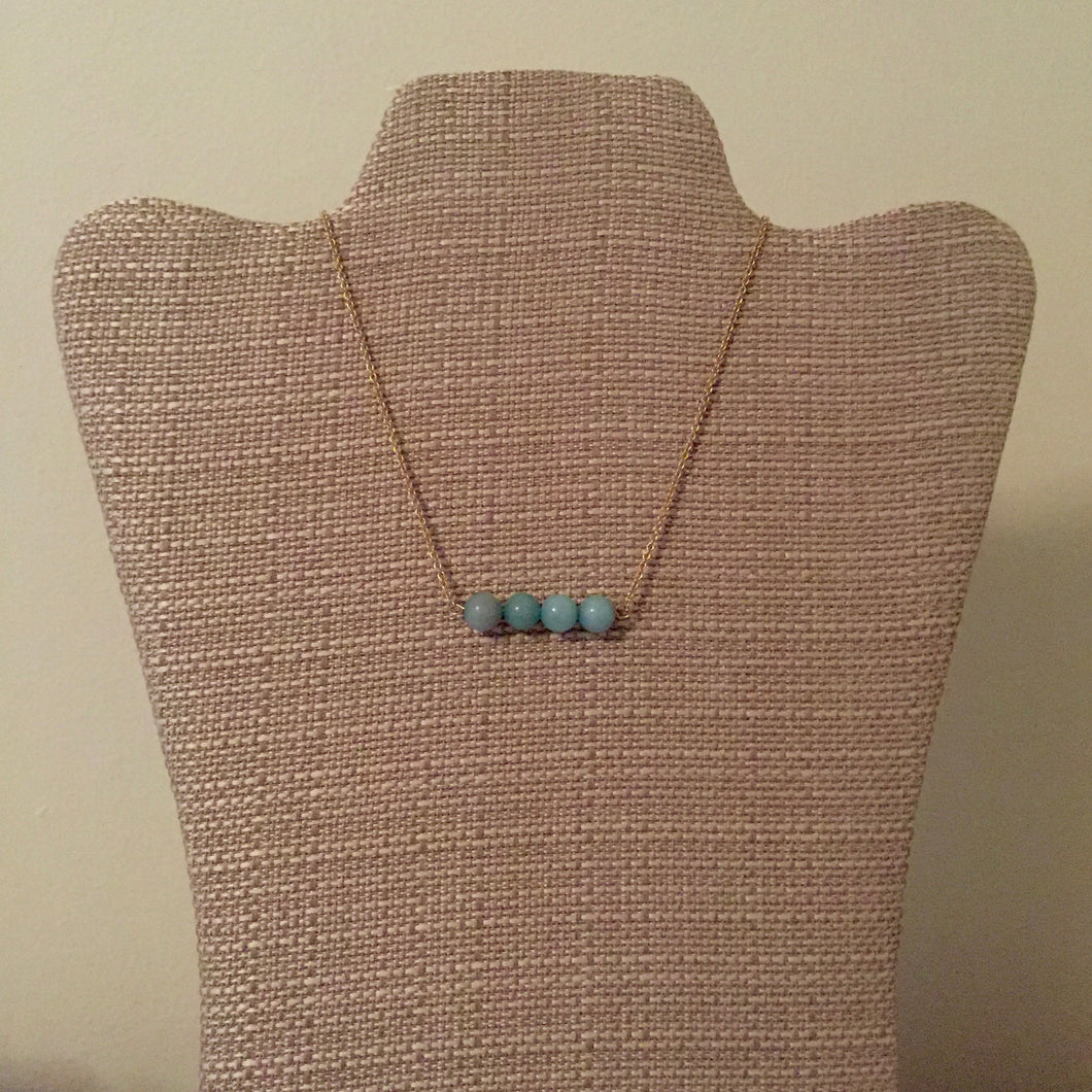 Delicate gold chain necklace with four pretty ocean blue stones. Casual, everyday style. Measures 17.5