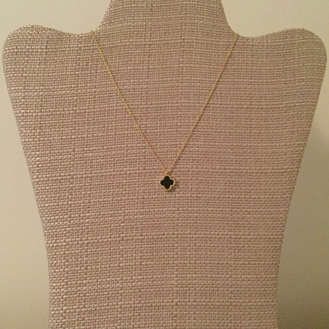 Reversible black and white clover pendant accented with gold. Reversible style to mix and match with many looks. Measures 15.5