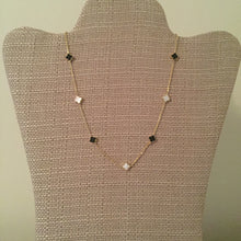"Dainty gold chain adorned with chic black and white clovers. Measures 15.75"" with a 2.25"" extension."