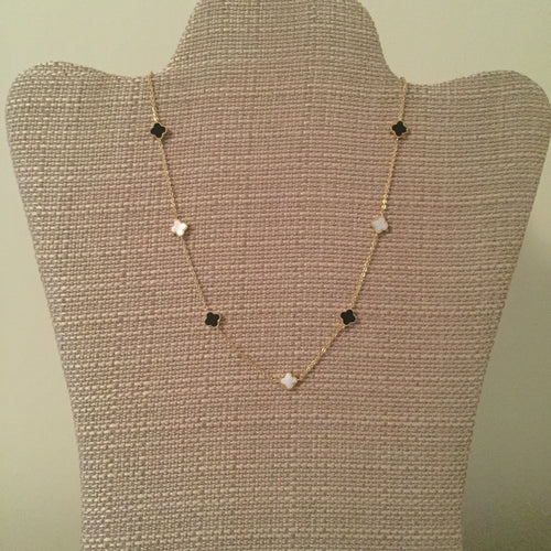 Dainty gold chain adorned with chic black and white clovers. Measures 15.75