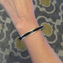 This black enamel cuff is perfect for stacking with your other favorite bracelets, and just as stylish when worn alone. Adjustable in size.