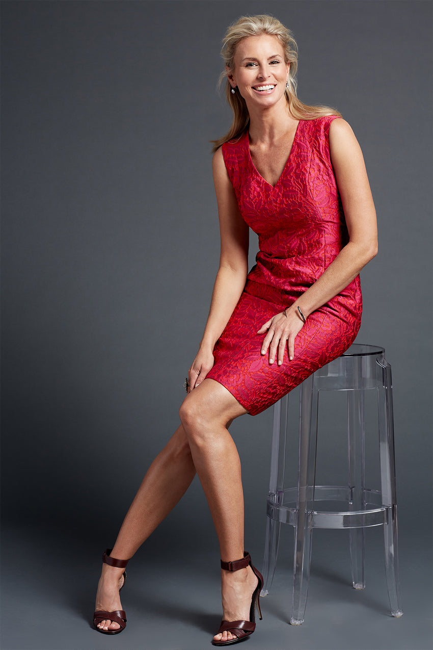 Brocade sheath dress in red with model sitting