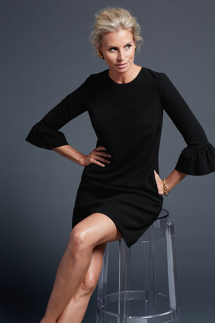 Bell sleeve a-line dress in black with model sitting