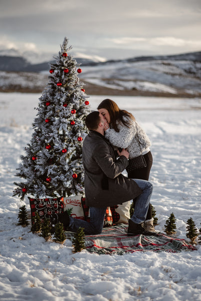 Man proposing in snow with christmas tree