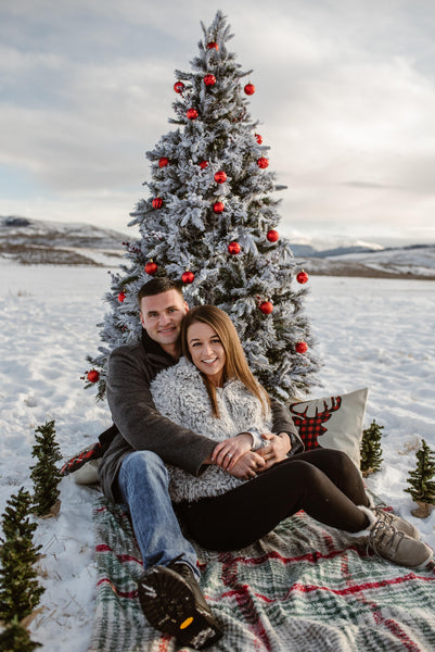 Couple snuggling in snow with christmas tree