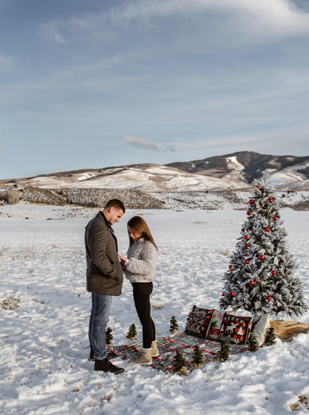 Couple engaged with christmas tree in snow