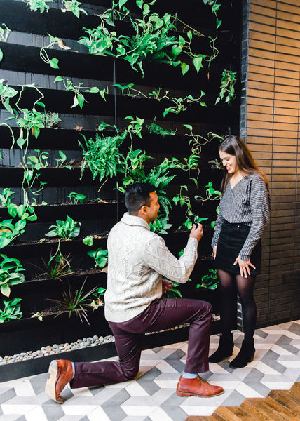 Man proposing in front of greenery