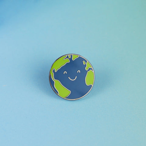 An Earth enamel pin sits on a blue background. The earth design has a cute smiling face.